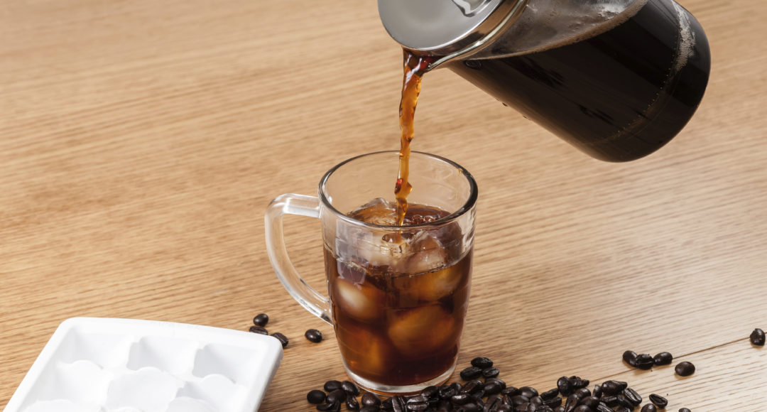 Pouring coffee over ice to make a full glass of iced coffee.