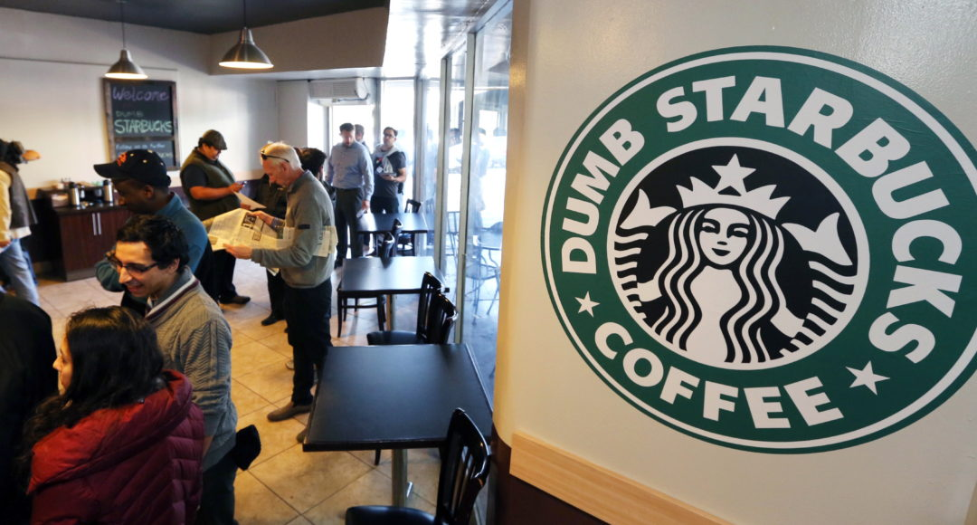 """People wait at Dumb Starbucks coffee in Los Angeles Monday, Feb. 10, 2014.  The store resembles a Starbucks with a green awning and mermaid logo, but with the word """"Dumb"""" attached above the Starbucks sign. Spokeswoman Laurel Harper says the store is not affiliated with Starbucks and, despite the humor, the store cannot use the Starbucks name. (AP Photo/Damian Dovarganes)"""